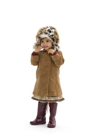 Laughing young girl wearing fur hat, brown coat and purple boots. Isolated on white background. photo