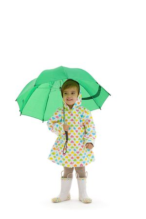 Happy small girl wearing raincoat and boots, holding green umbrella. Isolated on white background. photo