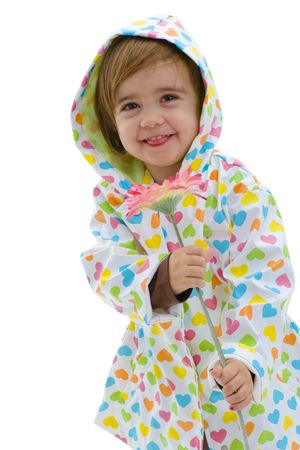 Happy girl child wearing raincoat and boots, holding pink flower. Isolated on white background. photo