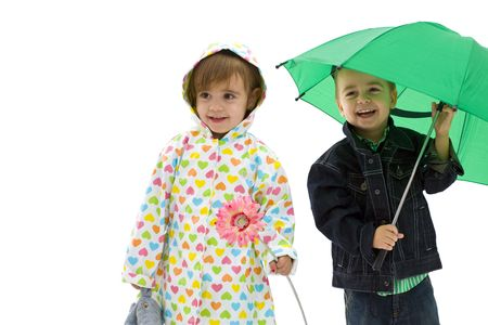 Happy laughing children. Boy holding a green umbrella. Girl wearing raincoat and holding flower. Isolated on white background. photo