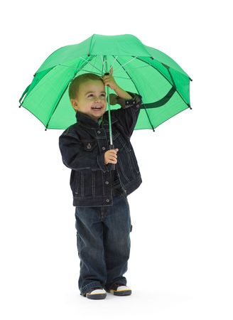 Preschoold boy wearing jeans jacket, holding green umbrella. Isolated on white background. photo