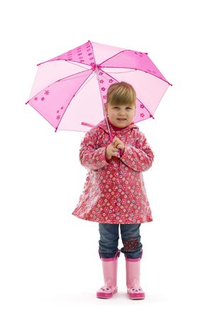 Small girl wearing raincoat with flowers and pink boots, holding pink umbrella. Isolated on white background. photo