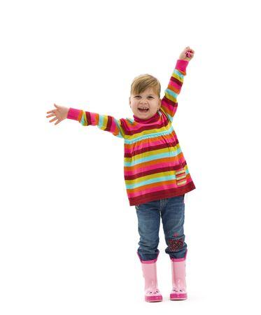 gente saludando: Ni�a feliz en el jersey de colores, pantalones vaqueros y botas de color rosa, riendo y agitando. Aislado en fondo blanco.