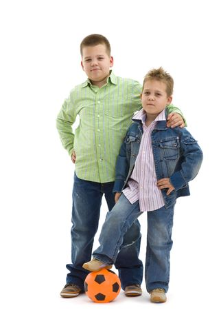 brother: Young boys wearing trendy jeans clothers posing togethers with football, on isolated white background.