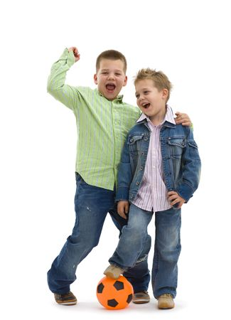 american children: Happy young brothers wearing trendy jeans clothers posing togethers with football, on isolated white background. Stock Photo