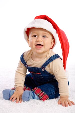 One year old baby boy in santas hat, smiling. photo