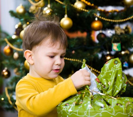Happy little boy opening Chrismas present at Christmas Eve under the Christmas tree. photo