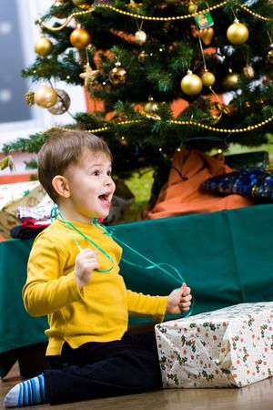 opening gift: Happy little boy opening Chrismas present at Christmas Eve under the Christmas tree.