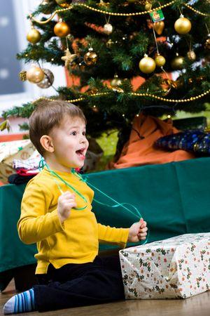 season opening: Happy little boy opening Chrismas present at Christmas Eve under the Christmas tree.
