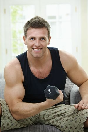 Muscular man sitting at home on sofa, doing excercise with hand barbell. photo