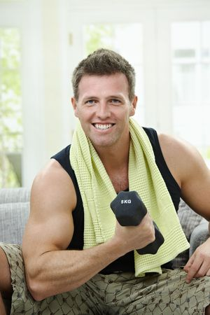 Muscular man sitting on sofa at home, doing excercise with hand barbell. photo
