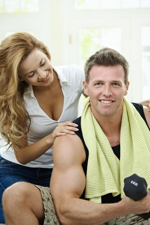 home gym: Muscular man sitting on sofa at home, doing excercise with hand barbell, her girlfriend embracing from behind.