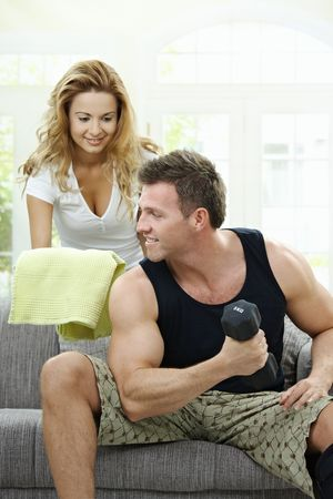 bringing: Muscular man sitting on sofa at home, doing excercise with hand barbell, her girlfriend bringing towel.