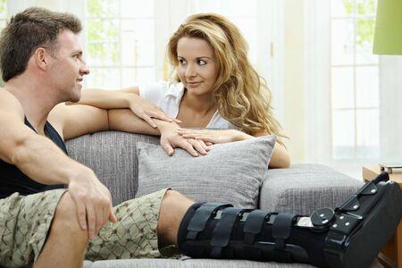 mann mit langen haaren: Love Paar zu Hause. Man ruht das gebrochene Bein auf dem Sofa, seine Freundin umarmt ihn von hinten.