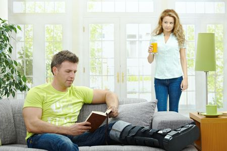 Man rasting his broken leg in cast on sofa at home, reading book. Woman bringing him orange juice. photo