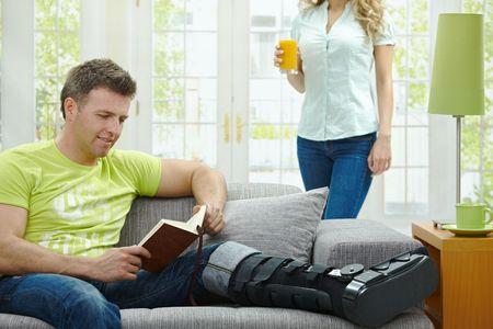 jambe cass�e: Man Rasting cass� la jambe dans le pl�tre sur le canap� � la maison, lecture de livres. Banque d'images