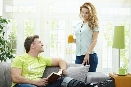 bringing: Man rasting his broken leg in cast on sofa at home, reading book. Woman bringing him orange juice. Stock Photo