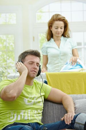 Husband sitting at couch listening music, wife ironing in the background, smiling. Selective focus on man. Stock Photo - 5732506