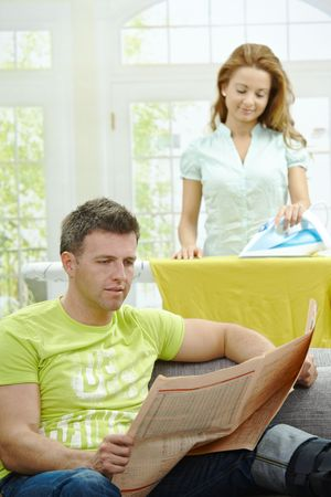 Husband sitting at couch reading news, wife ironing in the background, smiling. Selective focus on man. photo