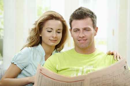 snug: Love couple reading newspaper together on couch at home, smiling.