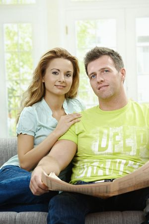 Love couple reading newspaper together on couch at home, looking at camera, smiling. Stock Photo - 5732511