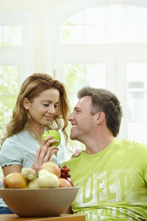 Love couple having breakfast together. Woman giving apple to her boyfriend. photo