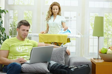 snug: Man with broken leg resting on couch, using laptop computer. Woman doing ironing at the background. Stock Photo