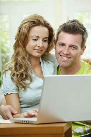 Couple using laptop computer at home together. Sitting on couch embracing,  looking at camera and smiling. photo