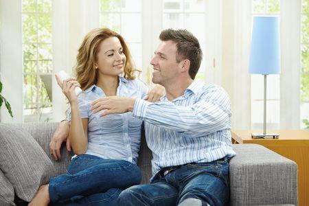 pareja viendo tv: Joven pareja viendo TV en casa, sentado en el sof�, manteniendo el control remoto en la mano.