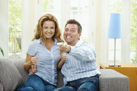 Excited couple watching TV at home, sitting on couch, holding remote control in hand. Stock Photo - 5732505