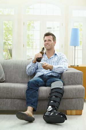 Man watching TV at home, sitting on couch, holding remote control in hand, drinking beer. photo