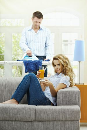 Happy woman sitting at couch watching TV, man ironing in the background. Selective focus on woman. photo