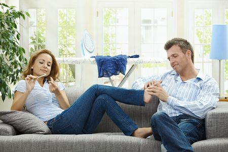 long feet: Couple relaxing at home on sofa, man giving foot massage to her gildfriend.