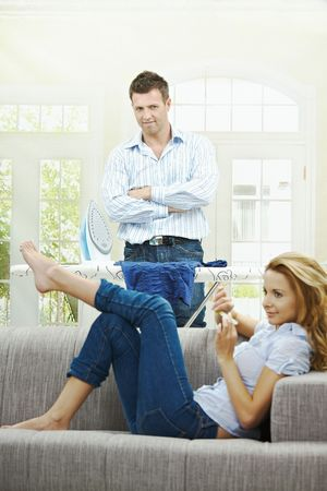 Relaxed young woman sitting on couch filing her nails, man watching with hands crossed behind ironing board. Focus on man. Stock Photo - 5732566