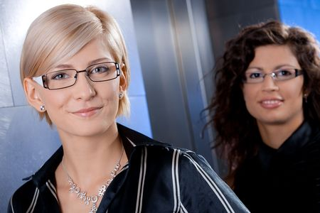 Closeup portrait of attractive young businesswomen, standing in office lobby, smiling. photo