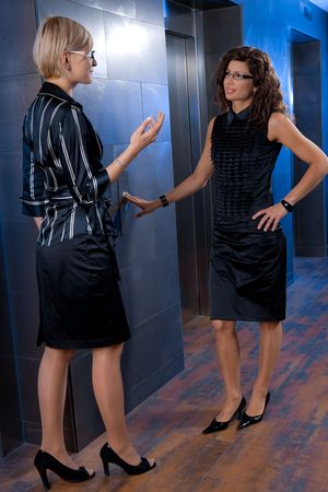 Attractive young businesswomen, waiting for lift, talking. photo