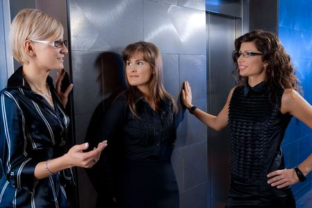 Group of attractive young businesswomen, waiting for lift in office lobby, talking. photo