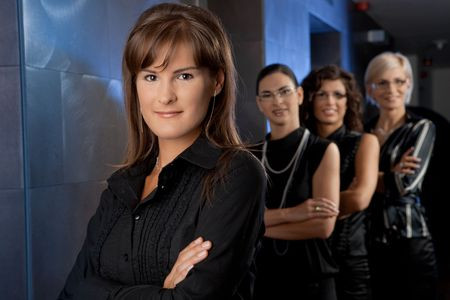 Team of attractive young businesswomen, waiting for lift in corporate ofiice lobby, smiling. photo