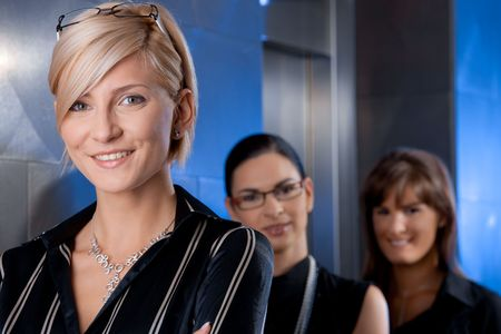 blond brown: Attractive young businesswomen, waiting for lift in office lobby, talking.