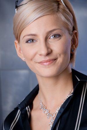 Indoor portrait of happy young businesswoman standing on office corridor, smiling. photo
