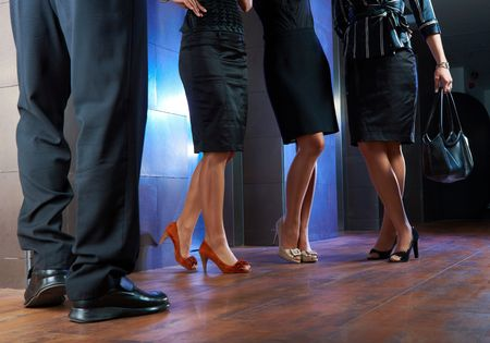 long skirt: Legs of businesspeople. Woman wearing skirt, stockings and high heels, man wearing dark trousers and shoes.