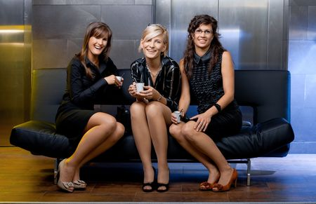 Group of young businesswomen sitting on couch in office lobby, haning a coffee break, smiling.