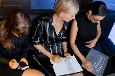 Team of attractive businesswoman having a meeting sitting on couch, using laptop computer and handheld. Overhead shot. photo