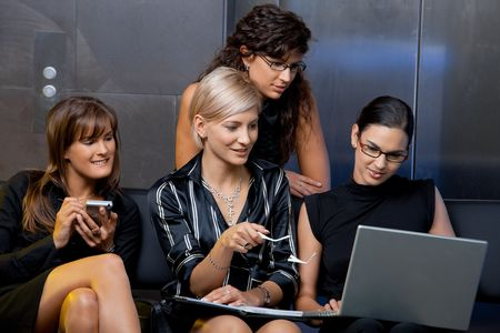 Team of attractive businesswoman sitting on couch, looking laptop computer screen, smiling. Stock Photo - 5742312
