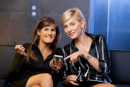 Young businesswomen sitting on couch at office lobby, using smart phone, smiling. photo