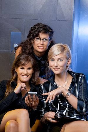 Young businesswomen sitting on couch at office lobby, looking at smart phone, smiling. photo