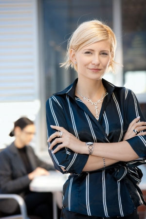 attire: Portrait of attractive young businesswoman standing arms crossed, smiling.