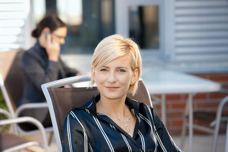 officetower: Portrait of attractive young businesswoman sitting in chair outdoor, smiling.