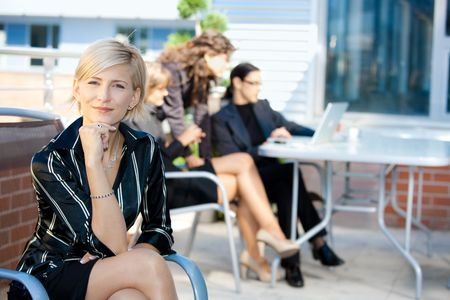 attire: Portrait of happy young businesswoman sitting in chair outdoor, smiling.