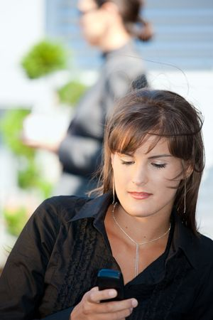 Young businesswoman using mobile phone, outdoors. photo